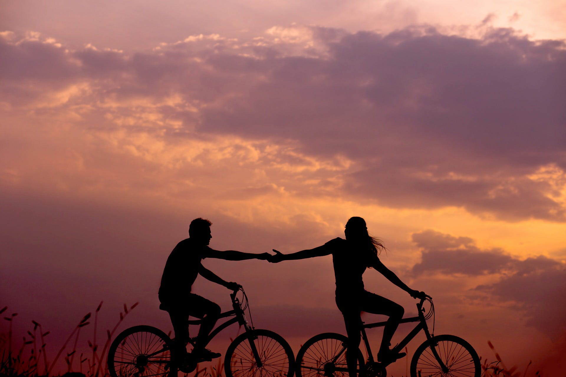 Two cyclists holding hands at sunset